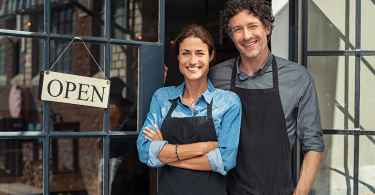 Two restaurant owners standing in front of an Open sign