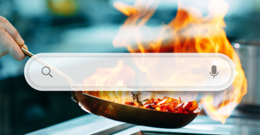 Internet search bar superimposed in front of a restaurant kitchen pan cooking with spurting flames